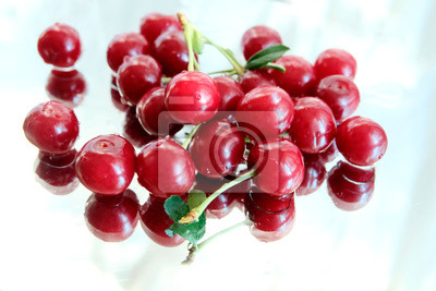 Summer red cherries scattered on a mirror table, texture, top view. Ripe fresh cherries from the garden. Berries and fruits concept.
