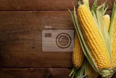 Tapeta Świeża kukurudza na cobs na nieociosanym drewnianym stole, zbliżenie. Widok z góry z miejsca na kopię