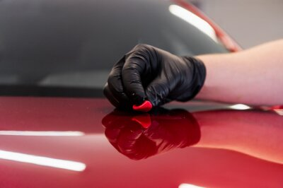 Tapeta The master removes small dirt pieces from the car bonnet surface with special clay before polishing. Professional car washing and detailing process.
