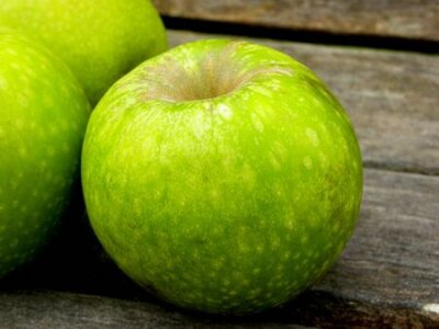 Tapeta three green apples on a wooden background