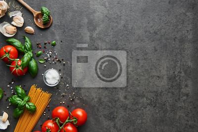 Tapeta Tło żywności dla smacznych dań kuchni włoskiej z pomidorami. Różne składniki do gotowania z spaghetti i łyżką. Widok z góry z miejsca na kopię.