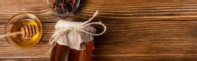 Tapeta top view of honey jar covered with craft paper near bowls with dipper and anise seeds on wooden table, banner