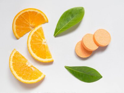 Tapeta Top view of vitamin c effervescent tablets with fresh juicy orange fruit slice and green leaf on white table. Vitamins from foods or supplements choices. Health and medical concept.