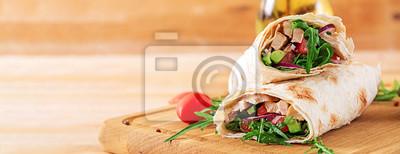 Tapeta Tortillas zawija z kurczakiem i warzywami na drewnianym tle. Burrito z kurczakiem. Transparent. Zdrowe jedzenie.