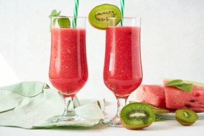 Tapeta Two glasses of fresh watermelon smoothie with kiwi and mint on a white wooden table