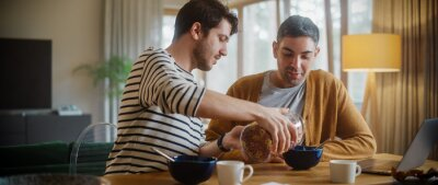 Tapeta Two Handsome Friends are Eating Colorful Breakfast Cereal in Cozy Kitchen in Stylish Apartment. Young Adult Gay Couple Have a Conversation While Eating Healthy Nutricious Food in the Morning.