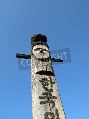 Uśmiechnięty drewniany idol na tle błękitnego nieba