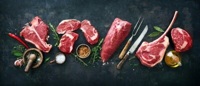 Tapeta Variety of raw beef meat steaks for grilling with seasoning and utensils