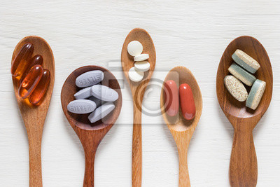 Tapeta Variety of vitamin pills in wooden spoon on white background, supplemental and healthcare product, flat lay surface