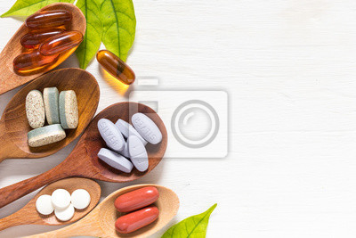 Tapeta Variety of vitamin pills in wooden spoon on white background with green leaf, supplemental and healthcare product, flat lay surface
