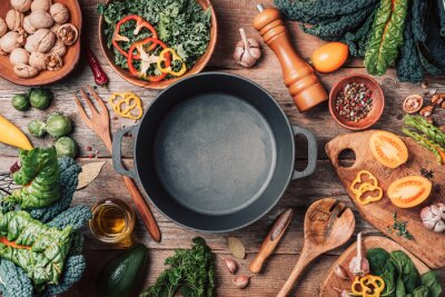 Tapeta Various organic vegetables ingredients and empty iron cooking pot, wooden bowls, spoons on wooden background. Top view, copy space. Organic vegetables ingredients for vegan cooking. Clean eating food