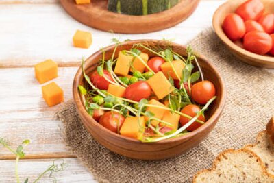 Tapeta Vegetarian vegetable salad of tomatoes, pumpkin, microgreen pea sprouts on white wooden background and linen textile. Side view, close up.