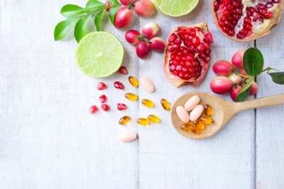 Tapeta Vitamin supplements on wooden spoon with healthy fruits berry, lime, pomegranete on white wooden background.Top view.