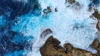 Tapeta Wild Ocean water from above - Waves hitting the rocks - aerial photography