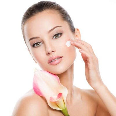 Tapeta Woman applying cosmetic  cream on a face. Fresh flower on the body