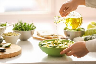 Tapeta Woman making salad with fresh vegetables in kitchen
