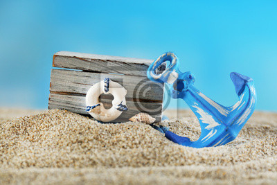 Wooden box with lifebuoy and anchor on sand on blue background