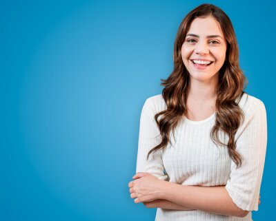 Tapeta Young Latin woman wearing casual clothes happy face smiling with crossed arms looking at the camera.