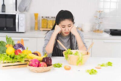 Tapeta Young woman or housewife is bored of cooking, which consists of a variety of fruits and vegetables for the family.
