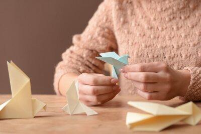 Tapeta Young woman with origami bird at table, closeup