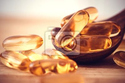 Tapeta Zamknij kapsułki z olejem rybim z witaminy D i Omega 3 na drewnianej płytce, aby zapewnić dobre zdrowie mózgu, serca i zdrowia