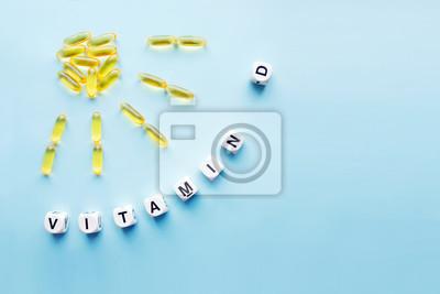 Tapeta Żółte kapsuły w postaci słońca z promieniami i słowo witamina D od białych kostek z literami na niebieskim tle. WITAMIN D słowo dla zdrowej i medycznej pojęcia. Witamina słoneczna